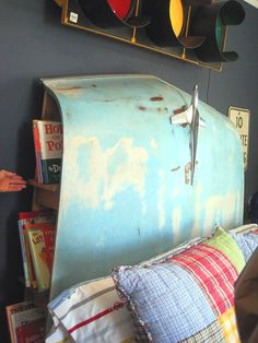 Headboard made from hood of weathered, classic car with hood ornament ('55 Chevy?). Notice book shelf storage on sides. Could also be wall art, minus the bed underneath. Depending on patina, dramatic lighting would be a plus for such a conversation piece find. Link leads to photo only, no turorial on how to secure/hang.