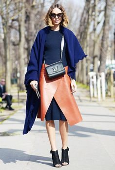 A leather wrap skirt is worn over a navy sweater dress and paired with an oversized blue scarf and a black crossbody.
