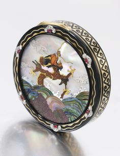 ENAMEL, MOTHER-OF-PEARL, RUBY AND DIAMOND POWDER COMPACT, CARTIER, 1929 The circular case with a hinged cover decorated with a mother-of-pearl and hardstone marquetry plaque depicting a dragon emerging from waves, within a gold and black enamel border enhanced with rose diamond and cabochon ruby motifs, opening to reveal a mirror, diameter approximately 60mm, signed Cartier, numbered, French assay mark, the Chinoiserie by Vladimir Makovsky.