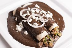 Recipe for vegetarian enchiladas with a quick mole sauce, filled with zucchini and mushrooms.