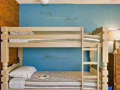 This traditional kid's bedroom features inspirational quotes above the bunk bed, which are painted neutral to offset the classic bedding.