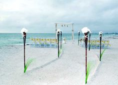 A perfect Florida beach wedding crafted by Suncoast Weddings - Dramatic sweeping aisle leads to a two post arch decorated with starfish