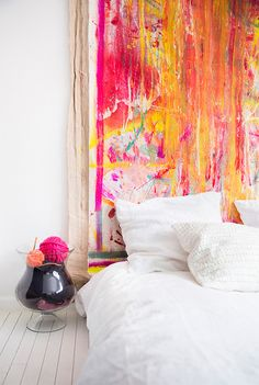 A white bed with a colorful art headboard