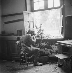 A sniper from the 3rd Infantry Division sitting in a chair in a kitchen with an open window, hidden by foliage in front of him,