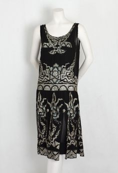 Beaded and sequined flapper dress, c.1925. The flapper style with a matching under slip features a drop waist and flirty paneled skirt— perfect for dancing. Decorated with tiny silver sequins, black beads, and iridescent sequins, this fab dress is the personification of the free spirited, dance-till-dawn mood of the flapper era.