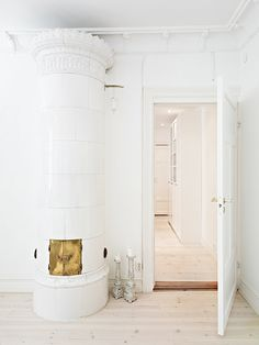 Ivory white painted room, cylindrical fire burning stove, light wood grain floors.