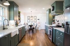 Green cabinets, white walls, black faucet