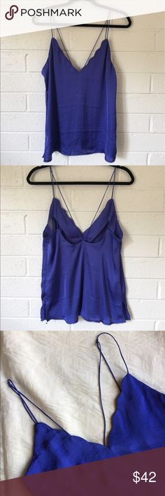 Free People Sensual Satin Scallop Deep V Cami This loose fitting periwinkle cami is everything! I own it in an orange and it makes for the perfect going out outfit! Pair with a cute bralette and you're set. The scallop deep v neckline and the criss cross detailing in the back adds some sexy touches. Size medium but it runs a little large. Fits more like a large. Free People Tops Camisoles