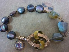 SAFE PASSAGE. My inspiration was an antique abablone gold filled watch chain with a two tone fob of a safe harbor. There is also a beautiful monogram on the back. I do not know where it is, but it reminds me of the harbor in St John in Newfoundland. To the abalone watch chain, I added