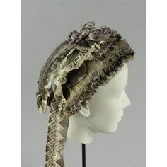 """Ca.1860-65 cap. Brim has a heavily stiffened white cotton net base with wires at front and back; it's 5"""" wide at slightly pointed at center top and narrowing to 1.5"""" wide, 8.5"""" down each side. Brim piece is first edged with white and black gauze-and-lace pleated trim. Layers of pleated lace and narrow velvet ribbon are then overlapped across it, ending in a layer of same pleated gauze. Connecticut Historical Society. [jrb]"""