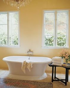 """A crystal chandelier strikes a whimsical note above a free-standing tub, which was chosen for its modern-looking flat rim. The owner likes the worn silk rug because """"you can stand on it with wet feet and it feels great."""" An antique painted tray table holds towels."""