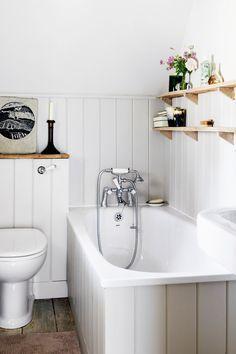 All-white bathroom with wood shelves above bathtub