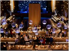Event lighting for a winter event. Twinkling lights in globes and stage backdrop conjure snow and stars, while candles represent a warm hearth.