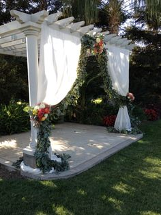 Silver dollar eucalyptus garland for wedding ceremony with tied-back curtain. Clusters of flowers using hydrangea, zinnias, China mums, dahlias, roses. In corals and oranges. By Fleurie