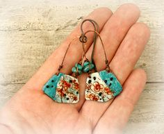 Torch fired enamel earrings, Turquoise earrings, rustic Boho earrings, colorful enamel earrings, Gypsy Bohemian earrings, copper ear wires.  These Boho beauties feature copper enamel charms in white and blue with red flowers. I paired them with beautiful genuine Turquoise beads. The ear wires are oxidized copper wire.  The length is almost 2.5 (6.3cm), including the ear wires.  If you are allergic for the copper ear wires i can replace them for antique brass colored non-allergenic niobium…