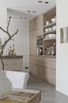 pale blond wood contemporary kitchen - floor to ceiling cupboards and built-in appliances in stainless steel