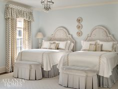 An upstairs guest room is packed with dressmaker details, including custom linens by Jacksonville, Florida's The Linen Ladies, crewelwork lumbar pillows from Ryan Studio, a Sister Parish pattern on the window treatments and chaise longue, upholstered headboards featuring a knotted motif, and upholstered benches with skirt pleats.