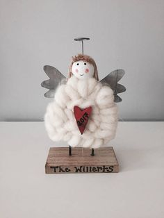 Personalised Decorative Standing Wooden Angel. Personalised with the family name and a year of your choosing. This festive wooden Christmas angel ornament is decorated in wood, metal and a soft wool. Height: 16cm  At Torys we love this novelty Christmas item ❤️