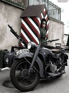 A Wehrmacht soldier stands guard at a military checkpoint in France. If somebody tries to pass through without authorization, the soldier keeps a BMW R75 motorcycle nearby in the event he must make pursuit.