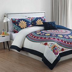 Bold boho style will brighten your space with the Ahimsa Comforter Set from VCNY. In ivory and purple, the set brings understated chic to your bedroom with a large circular floral medallion in pink, purple and blue tones, finished with a black border.