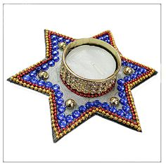 Purple Star Diya, Designer beautiful eye-catching wax diya in the shape of a star. Surrounded by purple and golden balls.