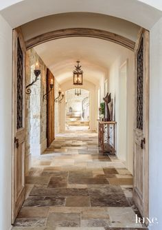 A French-style enfilade leads to a stairway. J. Nicolas Architectural Imported Hardware supplied the lanterns and fabricated additional sconces to match existing pieces from the owners' collection. Lime plaster by Palmer Masonry of Costa Mesa faces the walls, and antique Dalle de Bourgogne limestone from Exquisite Surfaces covers the floors.