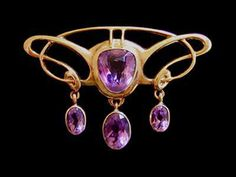 BARNET HENRY JOSEPH  An Art Nouveau gold brooch set amethyst with a three amethyst drops.  English. Circa 1900. Marked with Maker's mark and '9ct'.  Size: Height 2.9 cm. Width 4.3 cm. (Fitted case)