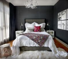 Cozy bedroom with black walls, sheer white curtains and a plush sheep skin rug at the foot of the bed with a tree stump stool