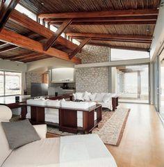 salon design avec parement en pierre et solives apparentes en bois