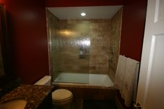 New tub and shower with ceramic tile and rain glass enclosure.