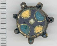 Late Saxon Cloisonné enamel gilt copper alloy disc brooch with seven lobes, each originally containing a glass sphere. ca 900 - 1099 AD. Found in the Quidenham area of Norfolk