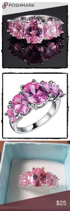 """4 carat """"Pink Ice"""" Pink CZ 5 stone Size 6 Jaw dropping, eye catching beauty! Made to look like a pink topaz (we won't tell if you won't!) White gold plated ring. These are deeply faceted 10 x 8 mm oval center stone, with two more oval stones on the side, 4 prong setting. The center stone reflects your present, the two side stones the past and future, and the smaller stones below that represent the journey you took to get to that place in life. This is a color of passion, beauty and elegance…"""