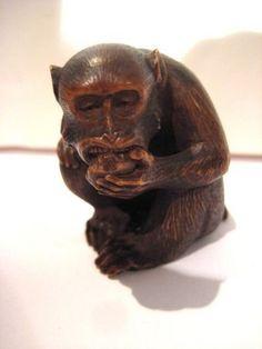 Japanese Netsuke ~ Monkey Eating Persimmon  ~  Boxwood  ~  19th century, Meiji Period, fur and paws naturalistically rendered.  Signed in an oblong cartouche Sinsei. 1.5 inches high.