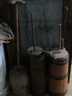 Butter churns in front of a tin door jelly cabinet.