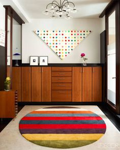 D'Urso designed the cabinetry in the entry, the small chest is by Harvey Probber, and the vintage chandelier is by Poul Henningsen