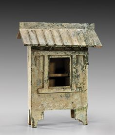 LARGE HAN DYNASTY GLAZED POTTERY HOUSE Unusually large, Chinese Han Dynasty, partially iridescent green glazed pottery model of a house; the rectangular form with single opening to the front: set on four shaped feet, and with separately modeled sloped roof; H: 24""