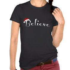Show everyone you are a Believer! Cute Holiday Shirt with Santa Hat on the word Believe, white letters on black