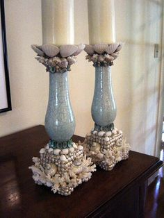 "These statement candlesticks will take center stage in your room design. Heavy terra cotta candlesticks with beautiful aqua crackle glaze become a treasured classic with the addition of lace and other corals, pearl turbos, patterns of pearled umbonium, coral, white pectins and richly colored turquoise limpets. Perfect for a traditional sideboard or dining room table, they measure a substanital 14"" tall and the base is over 5"" square."