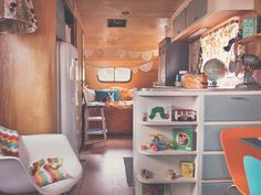This 23-foot 1950 Spartanette trailer, filled with a mix of vintage finds, handmade creations, and carefully curated furnishings, is home on the road for Joy Prouty's family of six. An old typewriter table with drop-down sides serves as the kids' homeschooling desk as well as the family dinner table when pulled away from the wall. Vintage school lockers house quilts and linens, and the sofa opens flat into a bed for the kids. Mom and Dad nest in a doily-filled master bedroom. See more at…