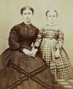 SKIRT LENGTH. This picture, made in Randolph, VT, shows a mature woman with a skirt only inches from the floor in length and a little girl with a mid-calf-length skirt. When Papa said she was old enough to court for marriage, a young woman would lengthen her skirts and put up her hair. The decision was based on her ability to manage a house and be a wife and mother, not her age. Growth pleats in the little girl's skirt would be let out as she grew so she could wear the dress longer…