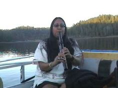 Mary Youngblood playing the native american flute on a pontoon boat in the late afternoon. No effects.