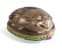 A RARE FABERGÉ SMOKY QUARTZ BONBONNIÈRE WITH JEWELLED AND ENAMELLED GOLD MOUNT, WORKMASTER MICHAEL PERCHIN, ST PETERSBURG, CIRCA 1900 carved in the form of a scarab with pharaoh's face, the eyes set with diamonds, the gold mount chased with leaf tips under translucent green enamel, cabochon ruby and rose-cut diamond-set thumbpiece, struck with workmaster's initials and Fabergé in Cyrillic, 72 standard,