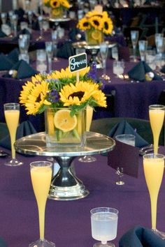 Love the small square centerpieces... blue table cloth, lemons and sunflowers & small blue flower accents!