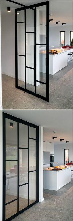 """Pivoterende deur met """"steel look"""" profielen en onderverdelingen op het glas. De deur is gemaakt van zwart geanodiseerd aluminium."""