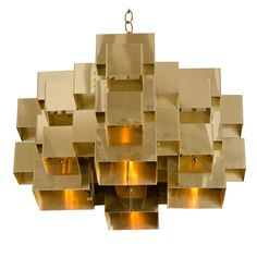 Polished Brass Cubist Chandelier by Curtis Jere, Signed  United States  1970's  A brass plated steel chandelier with folded interlocking sections, forming an intricate geometric cluster. By Curtis Jere. American, circa 1970.