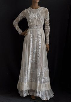 c. 1910 silk chiffon Edwardian tea dress with pin tucks, textured lace accents. Closes in back with small covered buttons and loops. Long narrow sleeves have tiny mother-of-pearl buttons to close the sleeves at the wrist. Tulle under-skirt is longer than the outer layer.