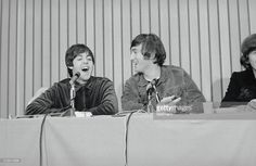 John Lennon (right) smiles as Paul McCartney speaks at press conference held after Beatles performance in Portland.