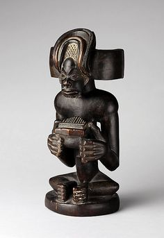 Commemorative figure of a chief playing a sanza (thumb piano) Date: 19th-20th century Geography: Angola Culture: Chokwe peoples Medium: Wood, kaolin Dimensions: Overall: 9 5/8 in. (24.5 cm)