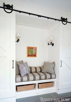 A bench is flanked by sliding barn doors that hide the children's cubbies on one side and a washer/dryer on the other.