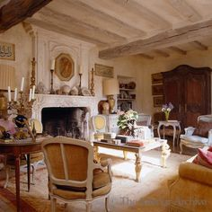 French country living room family room, bleached aged wood beamed ceiling, gorgeous carved stone fireplace, neutral pallette